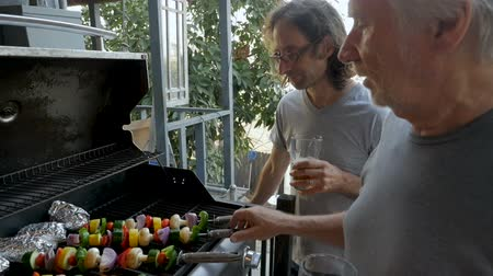 kebab : Tilt up from a bbq grill with vegetables to two men age 40 and 70 cooking outside together in slow motion