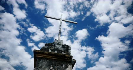 feltámadás : Time lapse of the clouds moving by an old cross against a blue sky - color graded