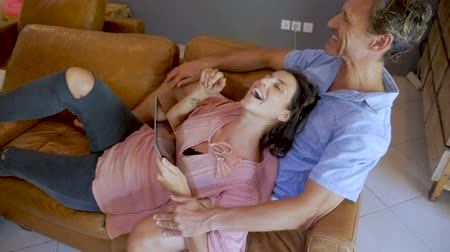 gyengéd : Overhead shot of a beautiful happy pregnant woman and handsome man using a digital tablet and laughing together in slow motion