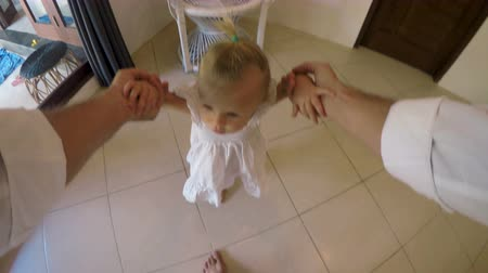 доверие : POV of a young baby girl taking her first steps with the help of her father holding her hands Стоковые видеозаписи