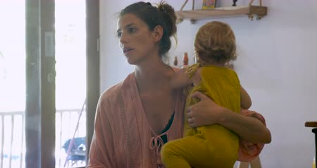 мать : Young attractive stay at home mother holding a toddler baby talking to someone off camera