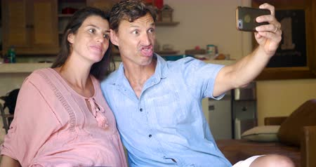 ostoba : Pregnant woman and man taking selfies with a mobile smart phone making silly faces, looking at the photos, and laughing at the photographs together on their app technology