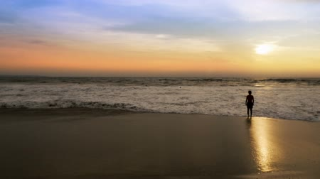tourist silhouette : Man watching the sunset as a the ocean wave gets his feet and legs wet in slow motion Stock Footage
