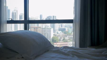 гостеприимство : Tilt up of a nice bed with comfortable pillows overlooking a modern urban city with tall skyscrapers