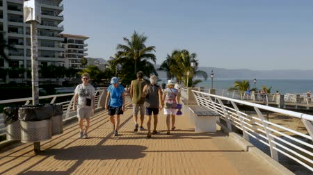 north america : PUERTO VALLARTA, MEXICO - CIRCA MARCH 2018 - People walking across a bridge on the malecon in slow motion