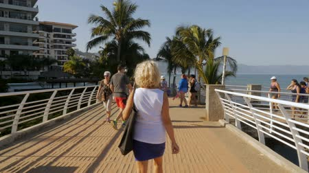 steady cam : PUERTO VALLARTA, MEXICO - CIRCA MARCH 2018 - Expatriates and tourists walking on the bridge over Isla del Rio Cuale on the Malecon in slow motion Stock Footage