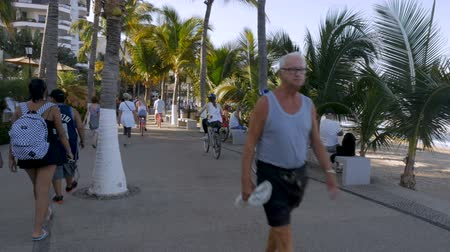 steady cam : PUERTO VALLARTA, MEXICO - CIRCA MARCH 2018 - Vacationers and expats walking and riding bicycles on the Malecon in slow motion Stock Footage