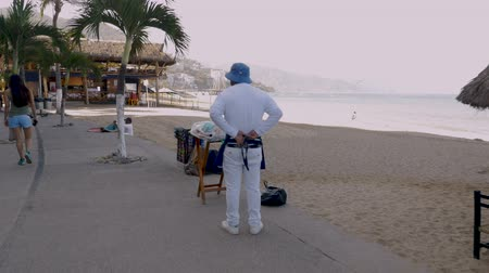 steady cam : PUERTO VALLARTA, MEXICO - CIRCA MARCH 2018 - Vendor tying his apron getting ready for his day of selling pastries off the Malecon on the beach in slow motion
