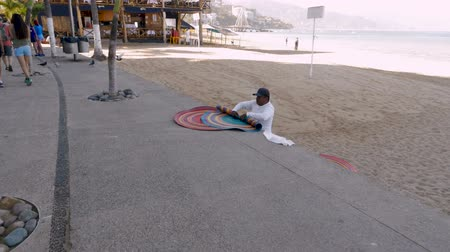 для продажи : PUERTO VALLARTA, MEXICO - CIRCA MARCH 2018 - Mexican vendor rolling up beach rugs for sale on the Malecon boardwalk Стоковые видеозаписи