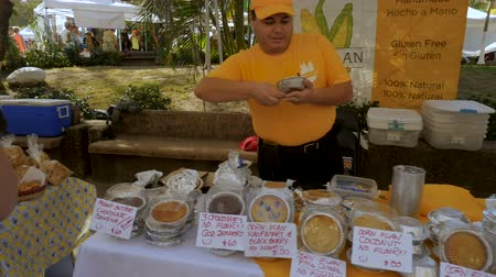 sobota : PUERTO VALLARTA, MEXICO - CIRCA MARCH 2018 - Mexican vendor giving out samples of gluten free food made of corn at the Saturday Market in slow motion Dostupné videozáznamy