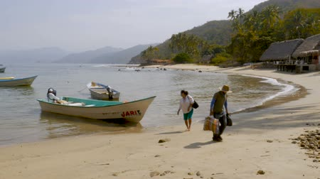 docking : Mexican man and woman getting off a water taxi in a calm bay off a boat and walking on an empty beach with a few thatched roof buildings in slow motion Stock Footage