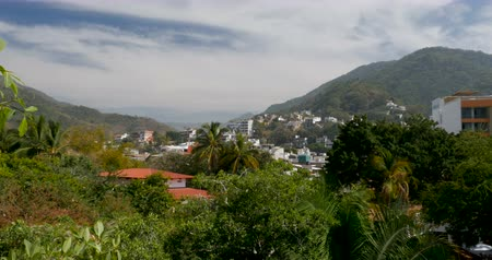 rivera : Establishing shot pan of houses and apartments built on a lush mountain forest or jungle in a tropical climate