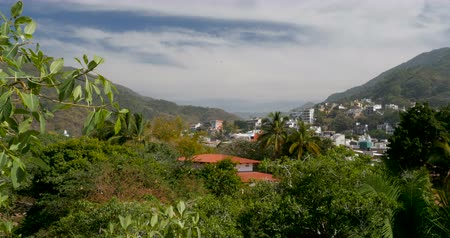 rivera : Pan of a view through a mountain valley with lush tropical jungle and houses looking towards vast wilderness in the distance Stock Footage