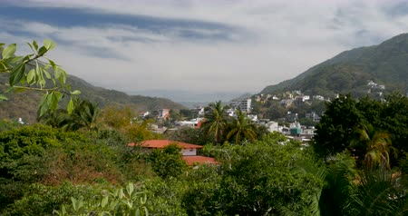 rivera : Establishing shot view through a mountain valley with lush tropical jungle and forest trees, houses, and apartments on the hillside