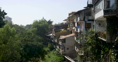 rivera : Establishing shot of many houses or apartments built on a hillside overlooking lush trees and a river Stock Footage