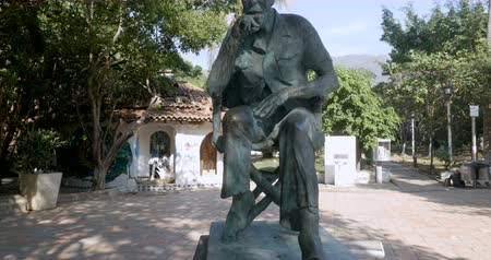 dyrektor : Crane up of the John Huston statue in the Rio Cuale park in Puerto Vallarta, Mexico