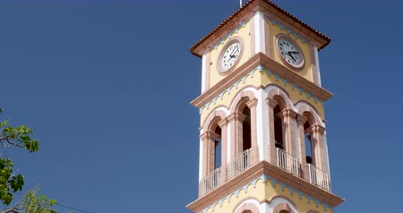 zegar : Establishing shot of the clock tower of the Parroquia de la Santa Cruz in Puerto Vallarta, Mexico against a clear blue sky Wideo