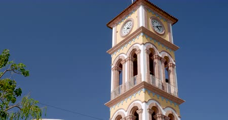 felhőtlen : Medium shot of the clock tower on top of the Parroquia de la Santa Cruz in Puerto Vallarta, Mexico against a clear blue sky Stock mozgókép