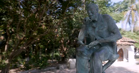 filmmaker : Camera circles around the John Huston statue in Isla Cuale park in Puerto Vallarta, Mexico