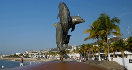 yunus : PUERTO VALLARTA, MEXICO - CIRCA MARCH 2018 - Crane up of a dolphin fountain statue and tourists on the Malecon enjoying their holiday vacation in the warm climate