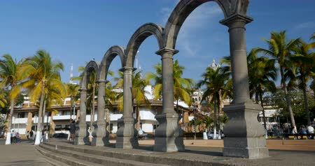 mexicano : PUERTO VALLARTA, MEXICO - CIRCA MARCH 2018 - people walking next to the The arches and plaza de armas along the Malecon with a view of the crown of the church of our lady Guadalupe during the day