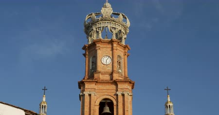 mexico city : Clock tower and crown of the Church of our lady Guadalupe, Puerto Vallarta, Mexico - locked down shot against a clear blue sky