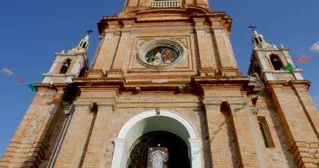 chrześcijaństwo : Tilt up low angle of the clock tower of the church of our lady of Guadalupe Puerto Vallarta, Mexico