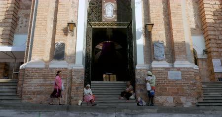 tek başına : PUERTO VALLARTA, MEXICO - CIRCA MARCH 2018 - A woman walks in the entrance of the church of our lady Guadalupe past three beggars sitting on the stairs