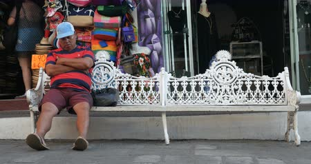 szieszta : PUERTO VALLARTA, MEXICO - CIRCA MARCH 2018 - Man sleeping on a metal park bench wakes up in front of a tourist shop