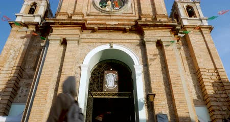 old times : PUERTO VALLARTA, MEXICO - CIRCA MARCH 2018 - Tilt down of tourists walking into the entrance of the church of our lady Guadalupe past three beggars sitting on the stairs