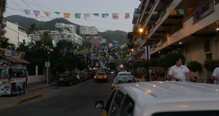 sobota : PUERTO VALLARTA, MEXICO - CIRCA MARCH 2018 - Active city life with workers and tourists on Olas Altas Street looking towards the condos and the mountains - dolly shot Dostupné videozáznamy
