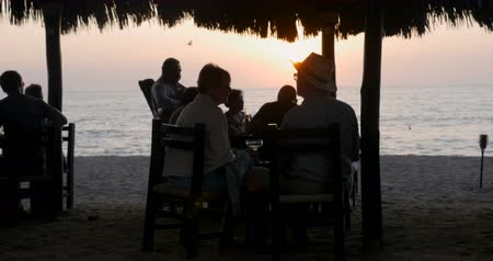 kuzey amerika : PUERTO VALLARTA, MEXICO - CIRCA MARCH 2018 - People eating at a restaurant at sunset with a musician playing a guitar for them on the beach under a shaded palapa