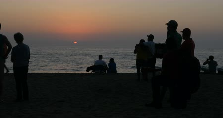mexico city : Silhouettes of people enjoying the sunset together on the beach including musicians, couples and people with their pet dog