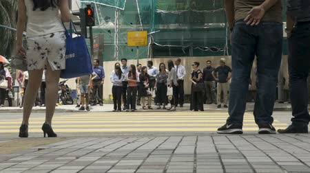 délkelet Ázsia : KUALA LUMPUR, MALAYSIA - CIRCA FEBRUARY 2018 - Asian people waiting at a crosswalk for a traffic light to cross a busy street - low angle slow motion