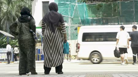 crossing road : KUALA LUMPUR, MALAYSIA - CIRCA FEBRUARY 2018 - Muslim women in burqas waiting to cross a street in slow motion
