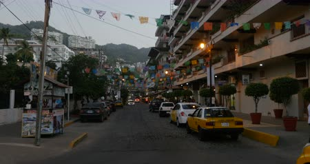 sobota : PUERTO VALLARTA, MEXICO - CIRCA MARCH 2018 - Banners, taxi cabs, and people at dusk on Olas Altas Street looking towards the condos and the mountains