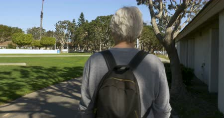 vándorlás : Camera following a happy healthy senior man with gray hair walking through a park with a small backpack on a beautiful sunny day - stabilized shot