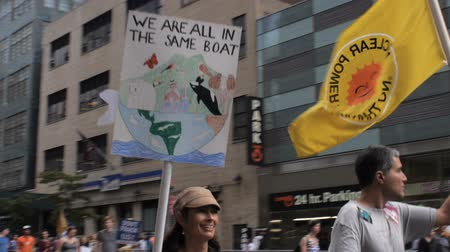 obnovitelný : NEW YORK CITY, UNITED STATES - SEPTEMBER 21, 2014 - Young attractive woman carrying a We are all in the same boat earth sign at the Peoples Climate March, a large-scale activist event to advocate global action against climate change.