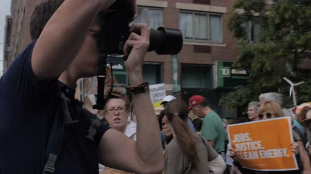 obnovitelný : NEW YORK CITY, UNITED STATES - SEPTEMBER 21, 2014 - A photographer or journalist taking photos with a camera at a protest at the Peoples Climate March, a large-scale activist event to advocate global action against climate change.