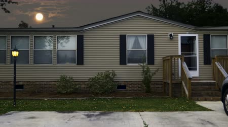 treyler : Establishing shot of a modest manufactured home with a full moon rising over its roof at night Stok Video