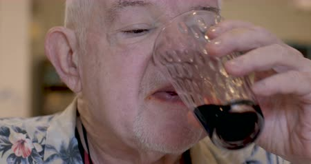 kırmızı şarap : Close up of an elderly senior man drinking red wine and chewing food in a restaurant or cafe Stok Video