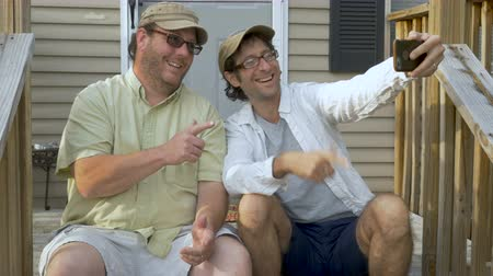 siding : Two happy men sitting on steps in front of a house taking a selfie with a smart phone