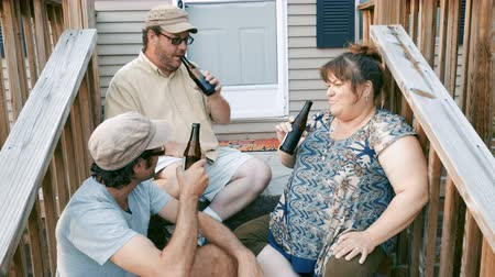 siding : Two men and one woman sitting on porch steps cheering with beer bottles and drinking - push in Stock Footage