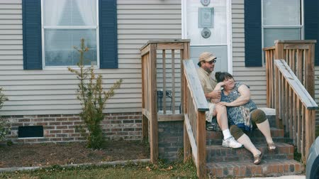 siding : A plus sized couple sitting on their porch steps talking and being affectionate - dolly shot