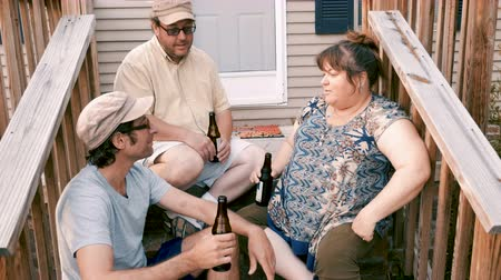 arrabaldes : Three friends including two men and a woman sitting on porch steps cheering with brown bottles and nodding their heads yes - push in Vídeos