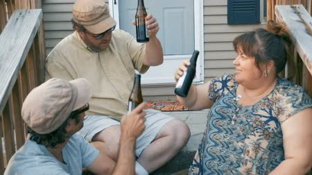 siding : Three happy friends in their 30s or 40s cheering and toasting with brown bottles sitting on steps in front of a house in slow motion Stock Footage
