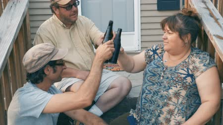 siding : Push in of three friends in their 30s or 40s sitting on porch steps cheering, toasting, and drinking a beer together in slow motion