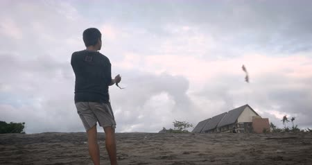 midair : BALI, INDONESIA - CIRCA JAN 2018 - Southeast Asian man flying a two handle stunt kite Stock Footage