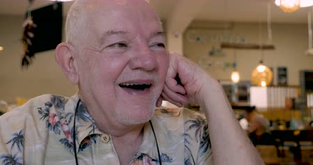 curto : Jovial happy elderly senior man in his 70s or early 80s laughing out loud in a restaurant or cafe Stock Footage
