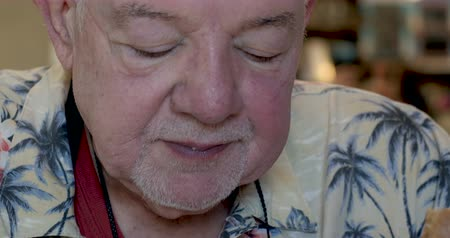 семидесятые годы : Close up of a senior man in his 70s or 80s eating a bowl of penne pasta with red tomato sauce and cheese wearing a Hawaiian shirt in a restaurant or cafe